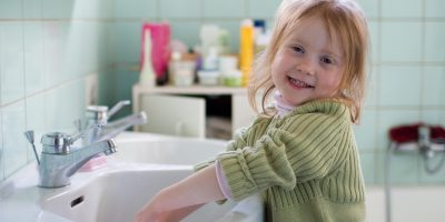 Smiling girl in bathroom, washing hands