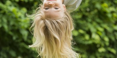 Child blond girl climbing on a rope upside down - summer playground